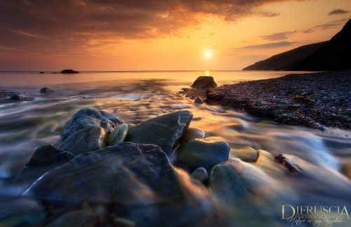 Dramatic sunrise landscape taken in Meat Cove, Nova Scotia displaying a seascape  complimented by a beautiful rocks, covered in rushing water and silouhetted mountains.